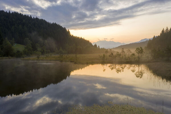 Aerial view of the misty sunrise over swamp of Pian di Gembro Nature Reserve, Aprica