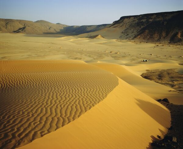 Dunes in canyon near Amguid, vehicle in the distance, Algeria, North Africa