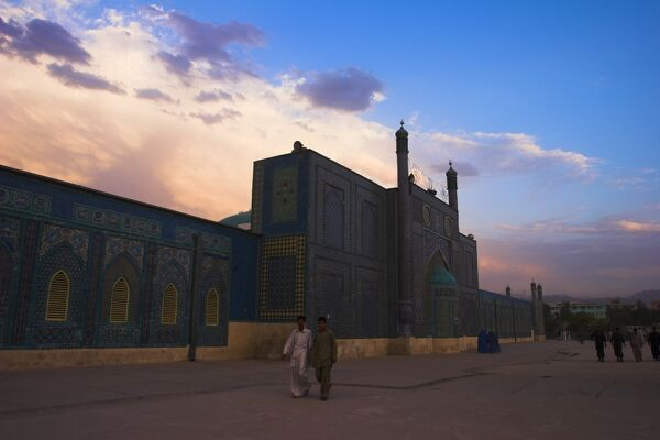 People walk at sunset past the Shrine of Hazrat Ali, who was assassinated in 661, Mazar-i-Sharif, Afghanistan, Asia