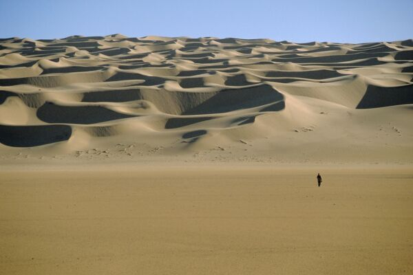 Sahara Desert with lone figure in foreground, Amguid, Algeria, Africa