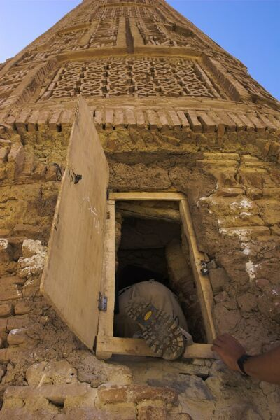 Tourist climbing into the minaret by a window, 12th Century Minaret of Jam, UNESCO World Heritage Site, Ghor (Ghur) (Ghowr) Province, Afghanistan, Asia