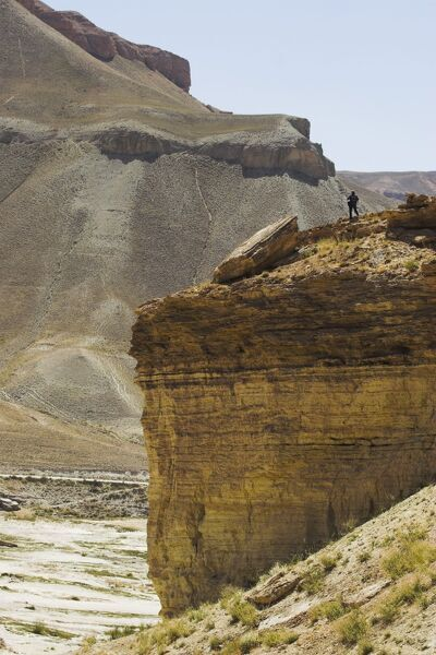 Tourist standing on rock cliff looking at Band-I-Zulfiqar the main lake, Band-E- Amir (Bandi-Amir) (Dam of the King) crater Lakes, Bamian province, Afghanistan, Asia
