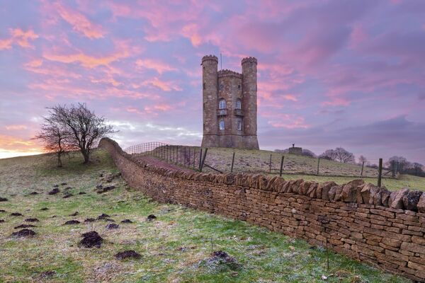 Broadway Tower and Cotswold drystone wall at sunrise, Broadway, Cotswolds, Worcestershire, England, United Kingdom, Europe