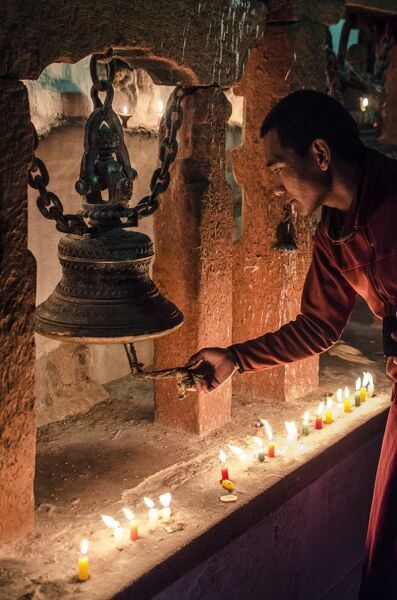 A Buddhist monk rings a prayer bell during the full moon celebrations, Bodhnath stupa, Bodhnath, Nepal, Asia