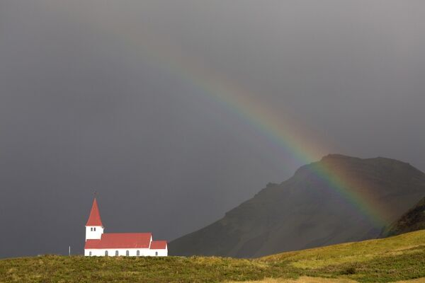 Church and rainbow against stormy sky and mountains, Vik Y Myrdal, South Iceland, Polar Regions