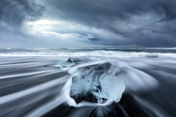 Glacier ice on black sand beach with waves washing up the beach on a stormy winter day, near Jokulsarlon, South Iceland, Polar Regions
