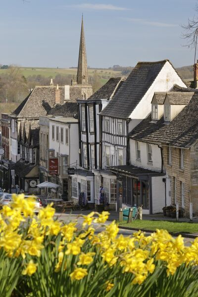 High Street and Burford Church with daffodils, Burford, Cotswolds, Oxfordshire, England, United Kingdom, Europe
