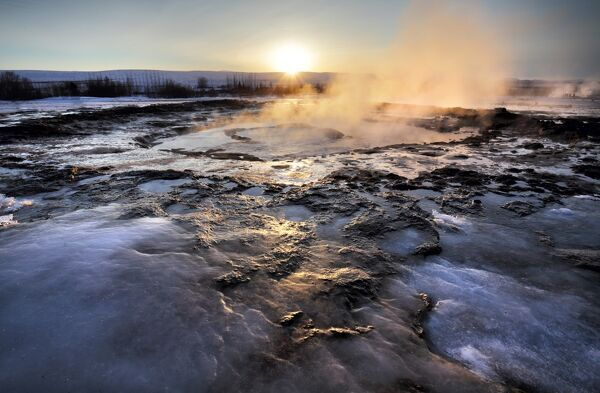 Hot pools and steam from Strokkur Geysir at sunrise, winter, at geothermal area beside the Hvita River, Geysir, Iceland, Polar Regions
