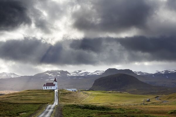 Ingjaldsholskirkja set against mountains on a dramatic stormy day, near Rif, Snaefellsnes Peninsula, Iceland, Polar Regions
