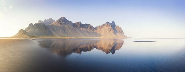 Panoramic view of Vestrahorn Mountain range reflecting in shallows of black volcanic beach, Stokksnes, South Iceland, Polar Regions