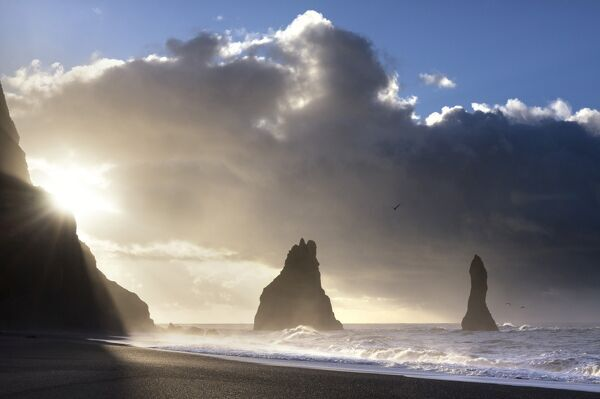 Rock stacks of Reynisdrangar in silhouette at sunrise, from Halsanefs Hellir Beach, near Vik Y Myrdal, South Iceland, Polar Regions