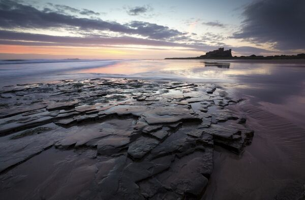 View towards Bamburgh Castle at sunrise from Bamburgh Beach, Bamburgh, Northumberland, England, United Kingdom, Europe