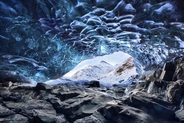 View from inside ice cave under the Vatnajokull Glacier towards snow covered mountains, near Jokulsarlon Lagoon, South Iceland, Polar Regions