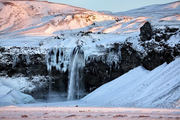 Winter view of Seljalandsfoss Waterfall bathed in evening light, South Iceland, Polar Regions
