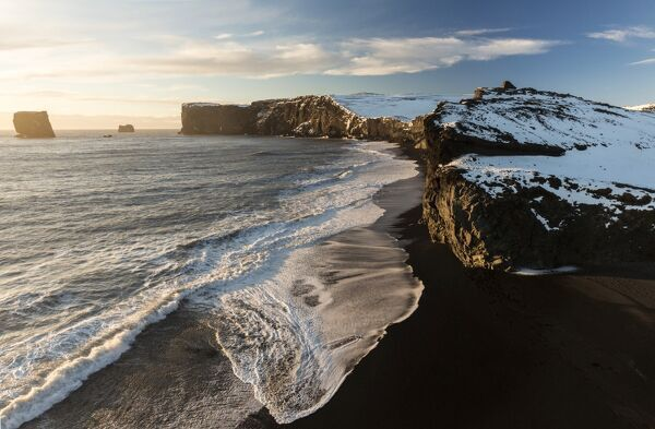 Winter view towards snow covered headland at Dyrholaey bathed in evening sunlight, near Vik, South Iceland, Polar Regions