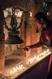 A Buddhist monk rings a prayer bell during the full moon celebrations, Bodhnath stupa