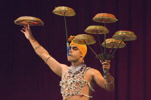 Man performing the Raban Dance and balancing drums in a tourist show at the Kandyan