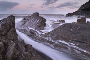 waves surge jagged rocks wildersmouth beach ilfracombe